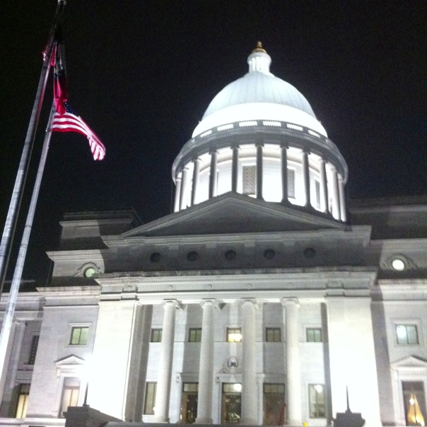 The red, white and blue stand out against the night sky and limestone of the Arkansas State Capitol.