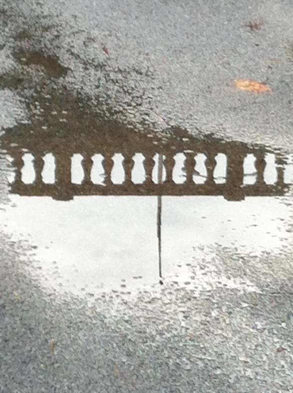 The Broadway Bridge balustrade reflected in a rain puddle.