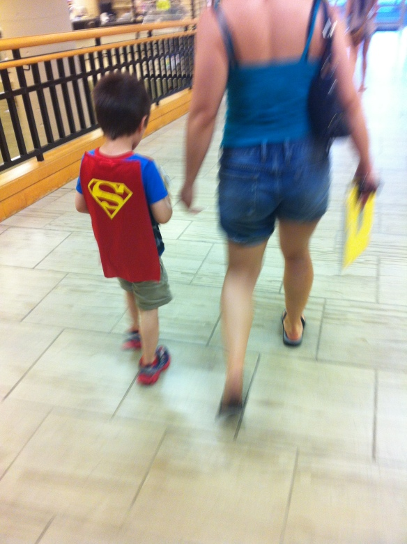 A Superhero and his mother leaving the library after checking out books and games.